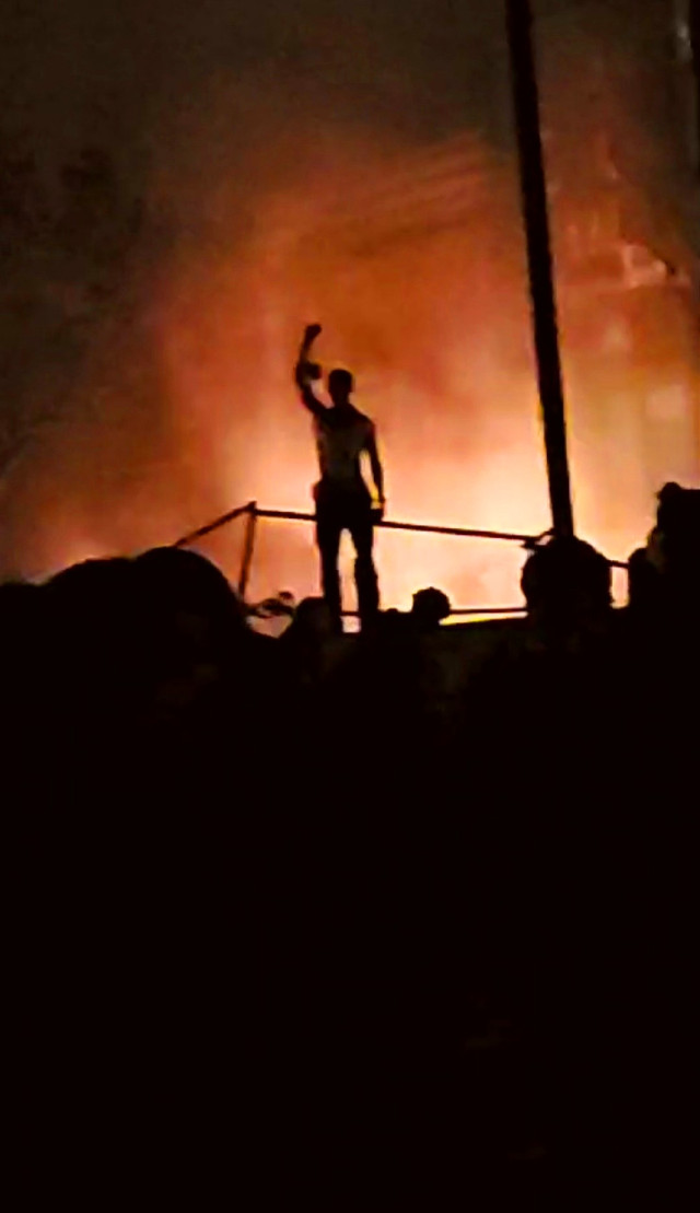 Symbol of Revolution... A man stands in front of the burning police station during a time of community uproar and unrest. Minneapolis, Minnesota Photo by: Parietal Imagination Art @pa, May 28th 2020 #minneapolis #revolution  #minnesota #protests #riots #georgeflynn #donotedit #myphoto #myphotography #vip #parietalimagination
