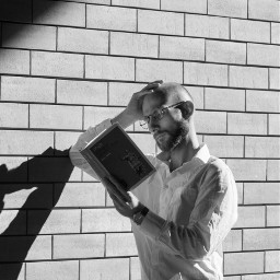 man model stylish portrait pose day light shadow book reading wall bricks pleinair urban city blackandwhite bnw photoshoot photo photography canon canon70d photoshop photoshopcs5 freetoedit
